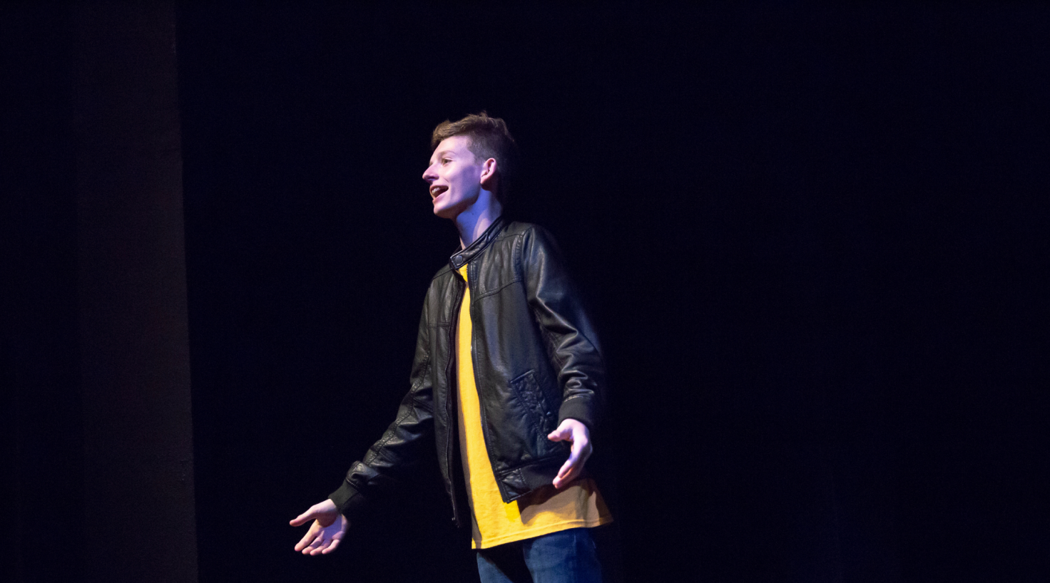 student wearing black leather jacked and yellow shirt singing on stage