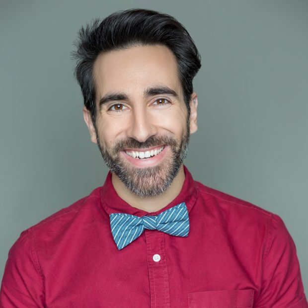 man in red shirt and bowtie smiling